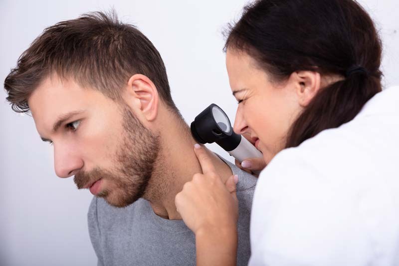 Man having his skin checked by a skin caner detection specialist